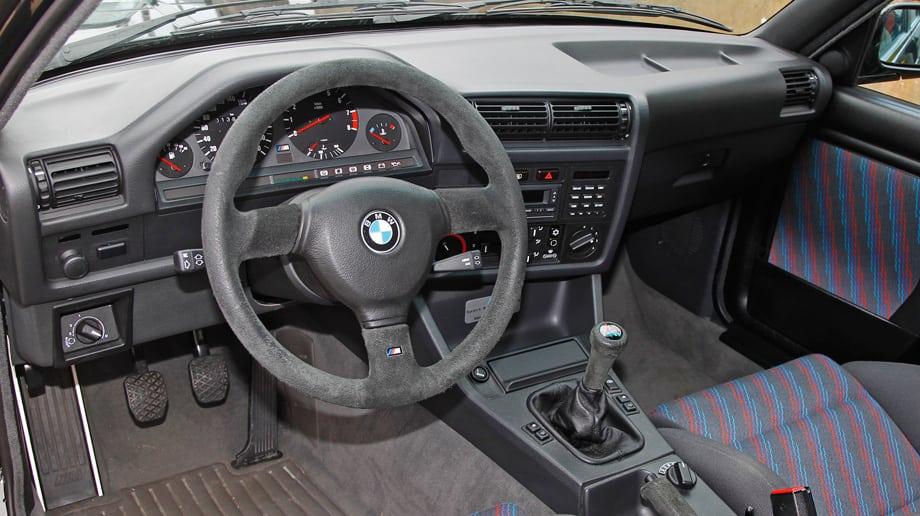 Интерьер модели Е30 оживляет пухлый руль, а на центральном тоннеле пристроен крупный тумблер управления трёхрежимными амортизаторами. Кстати, у Sport Evo регулируется ещё и передний спойлер с задним антикрылом.