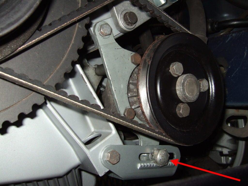 Замена приводных ремней на BMW 5 E34. Фото 4: Красная стрелка указывает на 19 мм винт натяжной шестерни.
