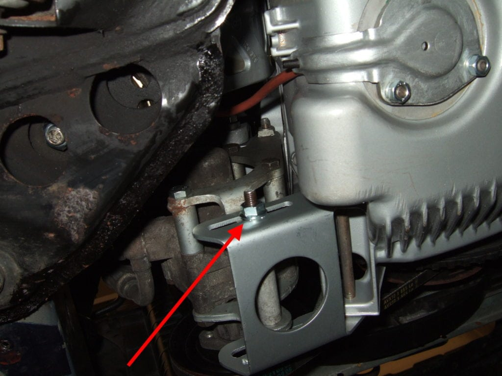 Замена приводных ремней на BMW 5 E34. Фото 5: Красная стрелка указывает на гайку на другом конце винта натяжной шестерни.