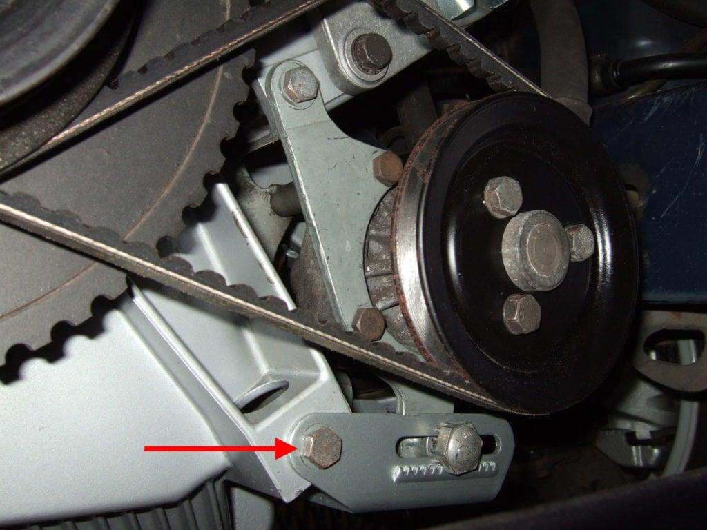 Замена приводных ремней на BMW 5 E34. Фото 6: Красная стрелка указывает на винт, ослабьте его на пару оборотов, чтобы облегчить регулировку.