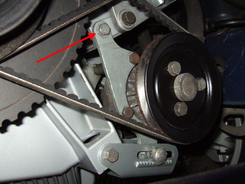 Замена приводных ремней на BMW 5 E34. Фото 7: Красная стрелка указывает на винт, ослабьте его на пару оборотов, чтобы облегчить регулировку.
